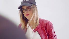Het model met heldere rode lippen stelt aan fotograaf tijdens fotozitting stock video
