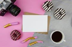 Het model met schone document spatie, koffie, retro camera en donuts, op geometrische pastelkleur gestreepte roze Vlakte als acht stock afbeelding