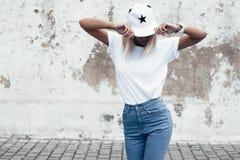 Het model stellen in duidelijke t-shirt tegen straatmuur stock foto's