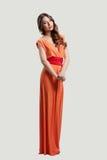 Het model stellen in oranje kleding Stock Foto