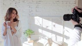 Het model stelt voor een foto in een overhemd en een bustehouder die zich door het venster bevinden stock videobeelden