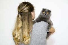 Het model is terug naar de camera en houdt de kat in zijn wapens aan het recht stock afbeeldingen