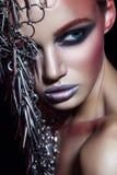 Het model van de manierschoonheid met metaal headwear en glanzende zilveren rode make-up en blauwe ogen en rode wenkbrauwen op zw stock foto