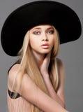 Het model van de maniertiener in een zwarte grote hoed in studio Stock Fotografie