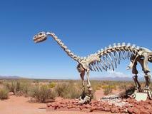 Het model van een dinosaurusskelet in het zand stock afbeelding