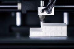 Het model van een huis wordt gecreeerd in 3D printer stock afbeeldingen