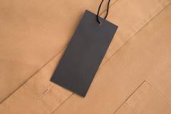 Het model van het etiketprijskaartje op beige overhemd Stock Foto's