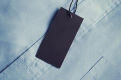 Het model van het etiketprijskaartje op zacht blauw overhemd Royalty-vrije Stock Fotografie