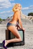 Het model zit op een oud televisietoestel Royalty-vrije Stock Afbeeldingen