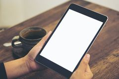 Het modelbeeld die van handen zwarte tabletpc met het lege witte scherm en koffie houden vormt op houten lijstachtergrond tot een Royalty-vrije Stock Foto