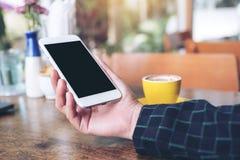 Het modelbeeld van een hand die witte mobiele telefoon met het lege zwarte Desktopscherm en gele koffie houden vormt op houten li Stock Foto's