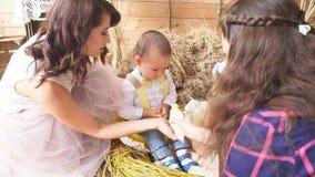 Het modelmamma legt zoon aan het meisje samen met de fotograaf voor stock videobeelden