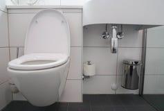 Het moderne badkamersbinnenland van witte ceramische toiletkom en de wasbak dalen met roestvrije bak voor afval royalty-vrije stock fotografie