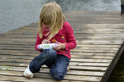 Het moderne jonge spel van de meisjes speelcomputer in aard Stock Foto
