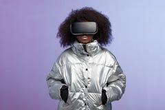 Het moderne krullende bruin-haired meisje gekleed in een zilveren-gekleurd jasje gebruikt de virtuele werkelijkheidsglazen stelt  stock foto's