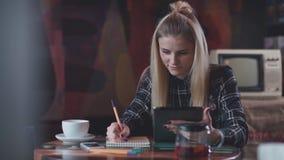 Het moderne meisje in een koffie het drinken thee, gebruikt de tablet en schrijft in notitieboekje stock video