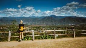 Het moderne meisje met tatoegeringen kijkt van boven een mooie mening van de stad van Pai Zij draagt een rugzak en een denim stock foto
