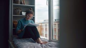 Het moderne meisje zit op vensterbank, luistert aan muziek en trekt in notitieboekje stock footage