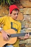 Het moderne musicus stellen met zijn gitaar Stock Afbeeldingen