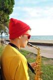 Het moderne musicus stellen met zijn saxofoon Stock Afbeeldingen