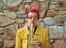 Het moderne musicus stellen met zijn saxofoon Stock Afbeelding