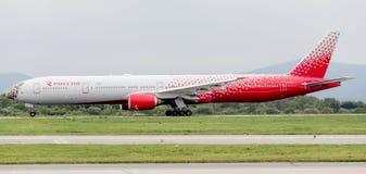 Het moderne passagiersvliegtuig Boeing 777-300 van Rossiya-Luchtvaartlijnen landt in bewolkte dag stock afbeelding