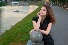 Het modieuze aardige meisje kijkt weg in park dichtbij rivier Stock Fotografie