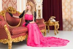 Het modieuze blonde in lange rode kleding zit op luxueuze bank stock fotografie