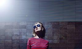 Het modieuze blondemeisje stellen in zonnebril, op een metaal gestreepte achtergrond Dag, openlucht Het wijfje kleedde zich in ge Stock Foto