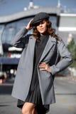Het modieuze donkerbruine meisje gekleed in een modieuze grijze kleding, een grijs jasje en een GLB stelt in de stadsstraat op zo royalty-vrije stock fotografie