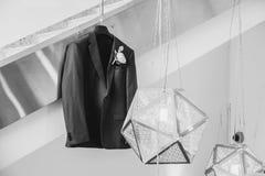 Het modieuze elegante kostuum van de huwelijksbruidegom met boutonniere het hangen in de ruimte royalty-vrije stock foto's
