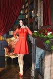 Het modieuze en sexy donkerbruine modelmeisje met krullend haar in rode modieuze kleding en in in rode schoenen bevindt zich dich royalty-vrije stock foto