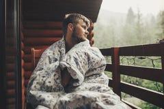Het modieuze gebaarde mens ontspannen op houten portiek onder bos in rai stock afbeelding