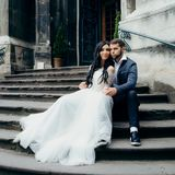 Het modieuze gelukkige jonggehuwdepaar koestert en houdt teder handen terwijl het zitten op de treden van oude barok Stock Foto's