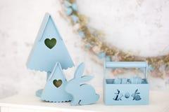 Het modieuze huisdecor in blauw is een houten mand, decoratieve het nestelen dozen en een leuk konijn De decoratie van Pasen De z royalty-vrije stock afbeeldingen