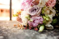 Het modieuze huwelijksboeket bloeit van struikrozen, eustoma en gouden trouwringen op de steen op de achtergrondaard Huwelijk cer royalty-vrije stock afbeeldingen