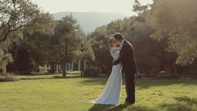 Het modieuze jonge huwelijkspaar kust elkaar stock videobeelden