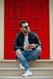 Het modieuze jonge mens stellen op achtergrond van rode deur in zonnige straat Stock Foto's