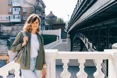 Het modieuze jonge vrouw stellen dichtbij stadsbrug Stock Afbeeldingen