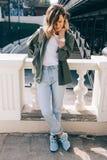 Het modieuze jonge vrouw stellen dichtbij stadsbrug Royalty-vrije Stock Afbeeldingen