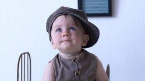 Het modieuze kind, leuke zuigeling in modieus kostuum kijkt rond tegen witte muur stock video