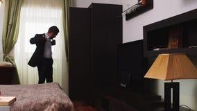 Het modieuze kostuum die van de mensenkleding zich dichtbij het venster in de slaapkamer bevinden stock videobeelden