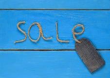 Het modieuze lege prijskaartje van denim op een koord rust op een blauwe pai Royalty-vrije Stock Afbeelding