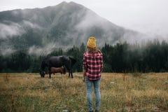 Het modieuze meisje bekijkt het paard over bergen in de mist royalty-vrije stock foto