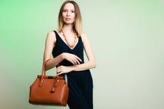 Het modieuze meisje die van de vrouwenmanier bruine handtas houden royalty-vrije stock foto's