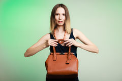 Het modieuze meisje die van de vrouwenmanier bruine handtas houden royalty-vrije stock foto