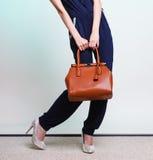 Het modieuze meisje die van de vrouwenmanier bruine handtas houden stock afbeeldingen