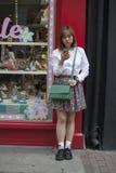 Het modieuze meisje die zich dichtbij de winkel met haar smartphone bevinden royalty-vrije stock afbeeldingen