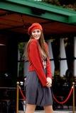 Het modieuze meisje gekleed in een grijze rok, een rode blouse op de t-shirt en rode baret stelt in de straat op de zonnige dag stock foto