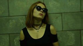 Het modieuze meisje in glazen bevindt zich in de avond op de straat dichtbij een muur stock footage